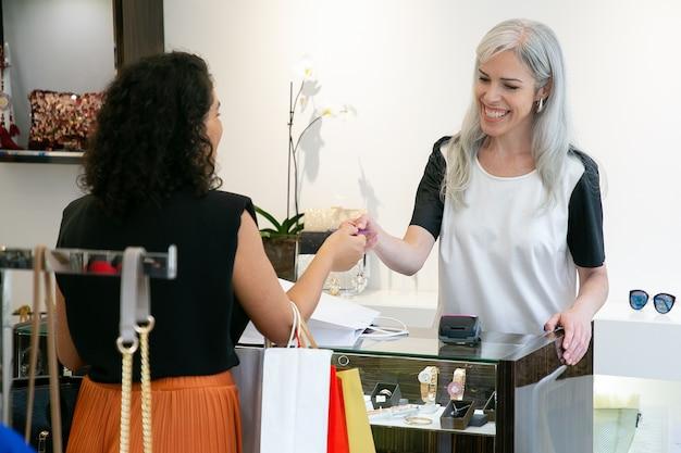 Caixa amigável feliz levando cartão de crédito do cliente para pagamento de compras, conversando, sorrindo e rindo. tiro médio. conceito de compras Foto gratuita