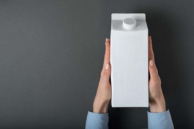 Caixa branca ou embalagem de tetra pack com uma tampa nas mãos femininas. Foto Premium