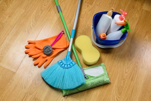 Caixa cheia de produtos de limpeza, esfregão, vassoura e luvas no fundo do  assoalho de madeira   Foto Premium