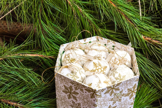 Caixa com bolas brancas de natal no fundo da árvore de natal Foto Premium