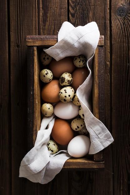 Caixa com codorna e ovos de galinha Foto gratuita