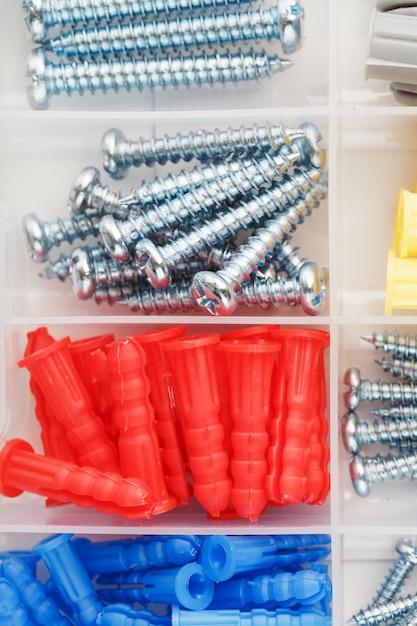 Caixa com vários parafusos e buchas para reparo e instalação Foto Premium