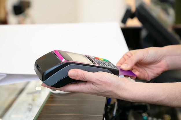 Caixa da loja operando o processo de pagamento e inserindo o cartão de crédito no terminal pos. tiro recortado, close-up das mãos. conceito de compra ou compra Foto gratuita