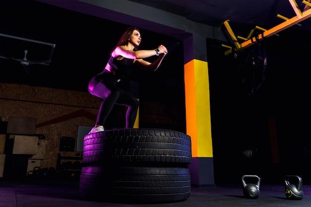Caixa de ajuste jovem pulando sobre pneus Foto Premium