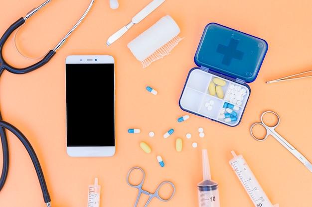 Caixa de comprimidos médicos; estetoscópio; telefone celular e equipamentos médicos em um fundo laranja Foto gratuita