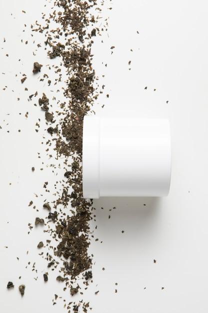 Caixa de creme de close-up e ervas no fundo branco Foto gratuita