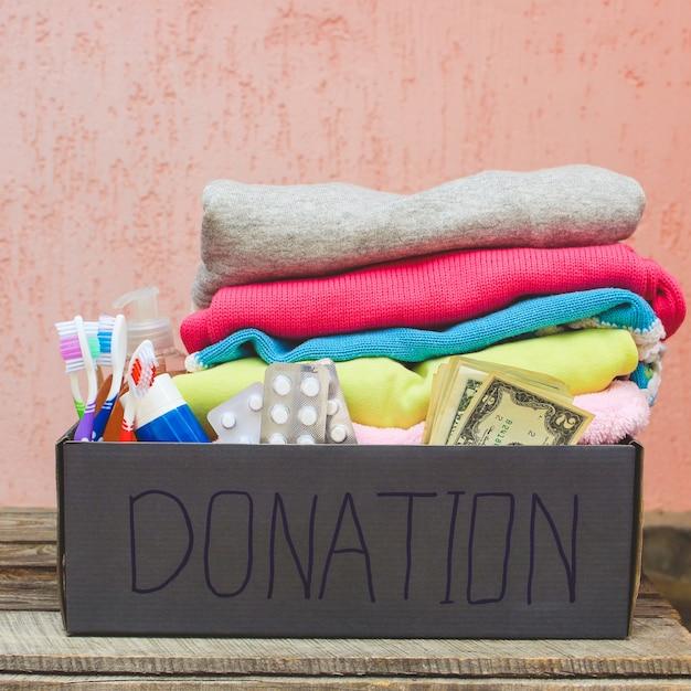 Caixa de doação com roupas, itens essenciais para a vida e dinheiro. Foto Premium
