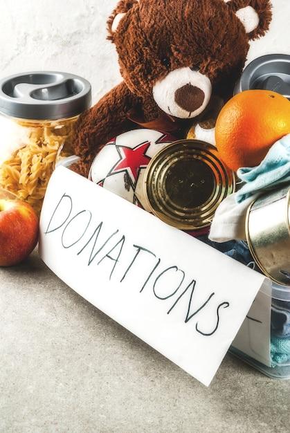 Caixa de doação de plástico com brinquedos, roupas e alimentos em fundo cinza branco Foto Premium