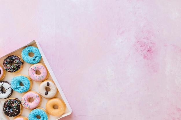 Caixa de donuts frescos em fundo rosa Foto gratuita