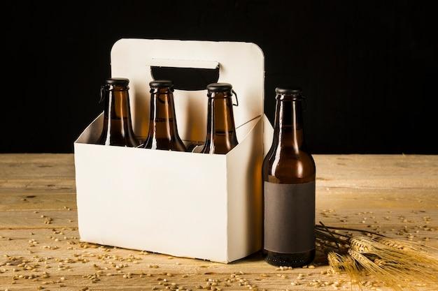 Caixa de embalagem de garrafa de cerveja e espigas de trigo na superfície de madeira Foto gratuita