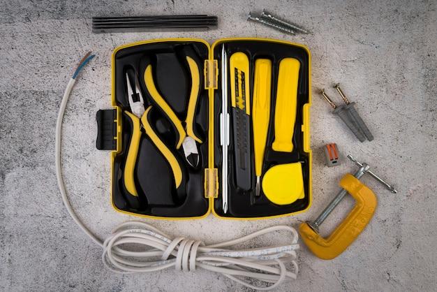 Caixa de ferramentas da vista superior com ferramentas amarelas Foto gratuita