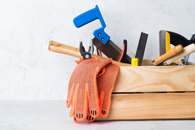 Caixa de ferramentas de madeira de close-up com ferramentas diferentes Foto gratuita