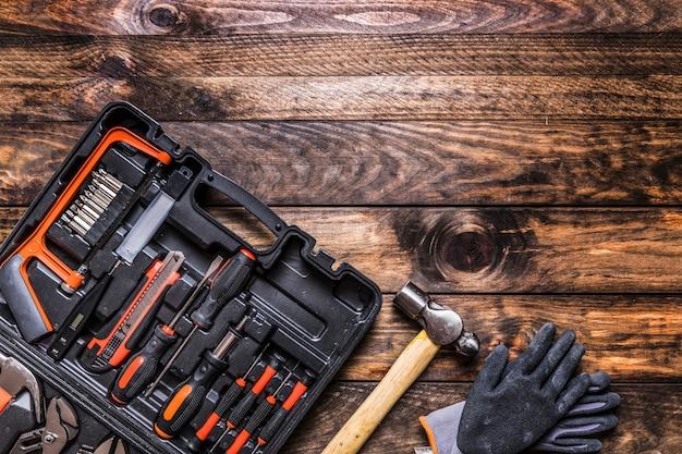 Caixa de ferramentas, martelo e luvas em fundo de madeira Foto gratuita