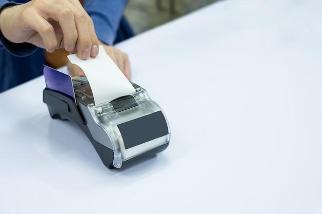 Caixa de funcionários rasgar papel de carta com cartão no terminal de pagamento Foto Premium