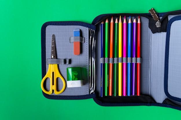 Caixa de lápis com fontes de escola em um fundo do papel verde com espaço da cópia. lay plana Foto Premium