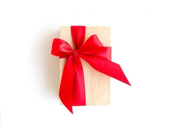 Caixa de madeira com fita vermelha no fundo branco com trajeto de grampeamento incluído Foto gratuita