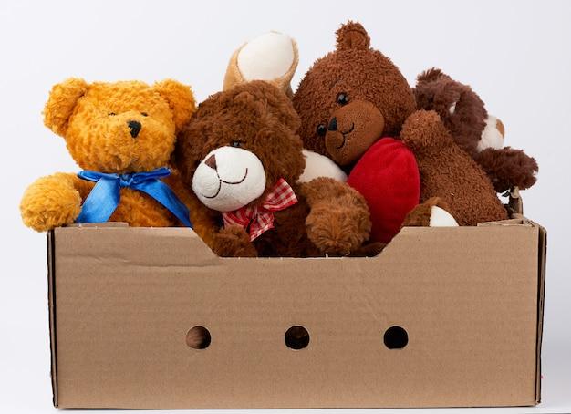 Caixa de papelão marrom com vários ursinhos de pelúcia Foto Premium