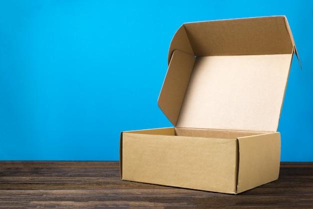 Caixa de papelão marrom fechada vazia para simulação em madeira escura Foto Premium