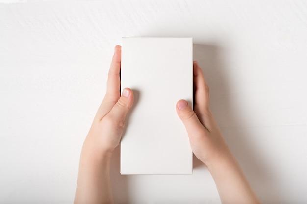 Caixa de papelão retangular branca nas mãos das crianças. Foto Premium