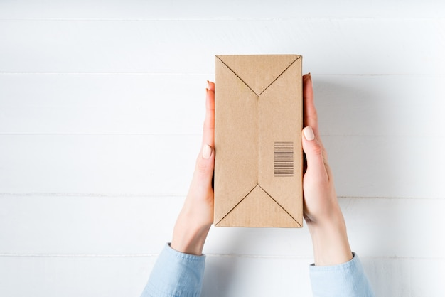 Caixa de papelão retangular com código de barras nas mãos femininas. Foto Premium