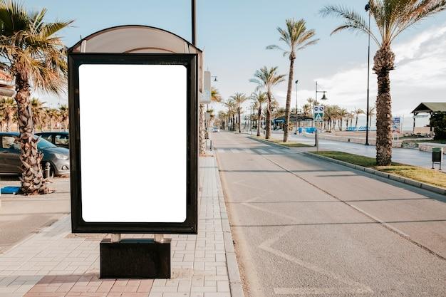 Caixa de parada de ônibus branco em branco na luz solar Foto gratuita