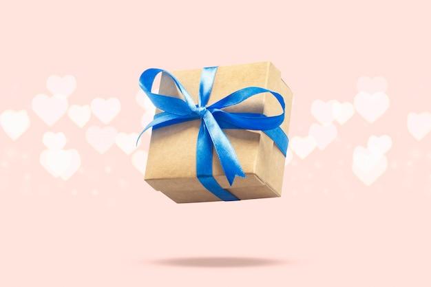 Caixa de presente a voar sobre uma superfície rosa clara com bokeh em forma de coração. conceito de férias, presente, venda, casamento e aniversário. Foto Premium