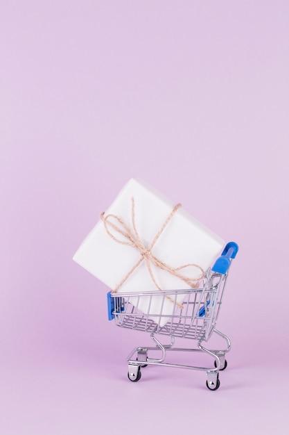 Caixa de presente, amarrada com barbante no carrinho de compras em fundo rosa Foto gratuita