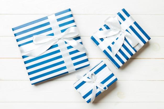 Caixa de presente bonita com um laço colorido na mesa de madeira branca Foto Premium