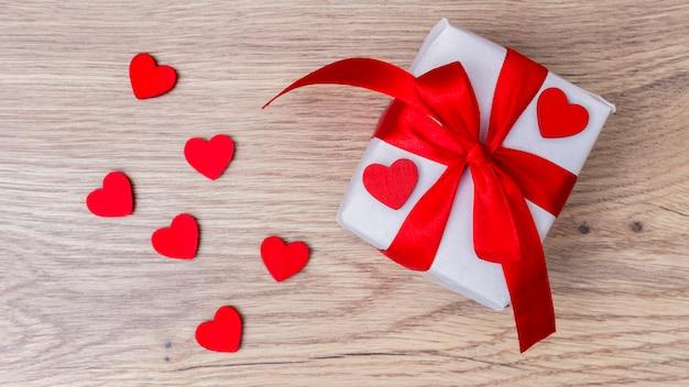 Caixa de presente branca com corações vermelhos na mesa Foto gratuita