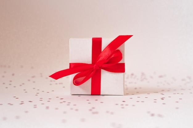 Caixa de presente branca com fita de cetim vermelha e arco e estrelas em um branco Foto Premium