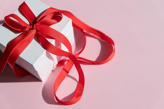 Caixa de presente branca com fita vermelha e laço Foto Premium