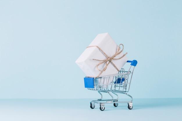 Caixa de presente branca no carrinho de compras no pano de fundo azul Foto gratuita