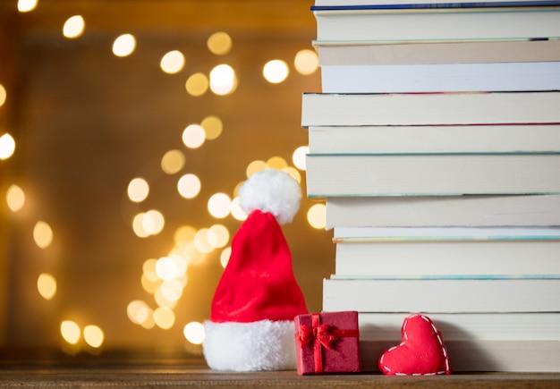 Caixa de presente, chapéu de papai noel e pilha de livros Foto Premium