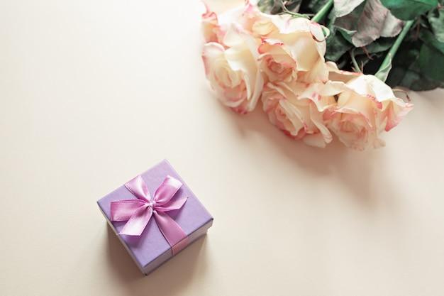 Caixa de presente com decorações e rosas na mesa Foto Premium