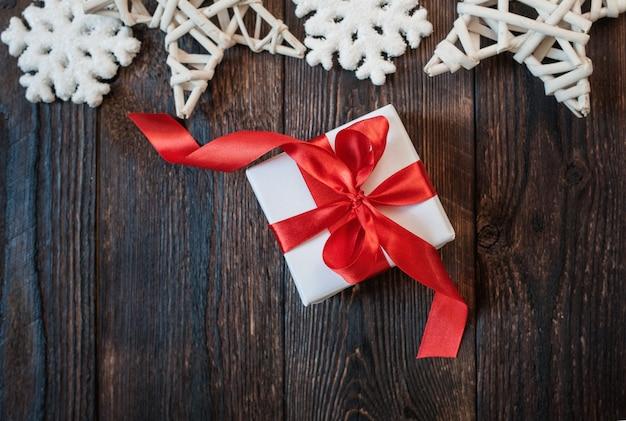 Caixa de presente com fita vermelha em um de madeira Foto Premium