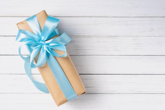 Caixa de presente com laço azul em uma superfície de madeira branca com espaço de cópia Foto Premium