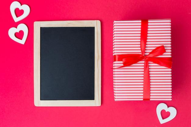 Caixa de presente com lousa e corações claras na mesa Foto gratuita