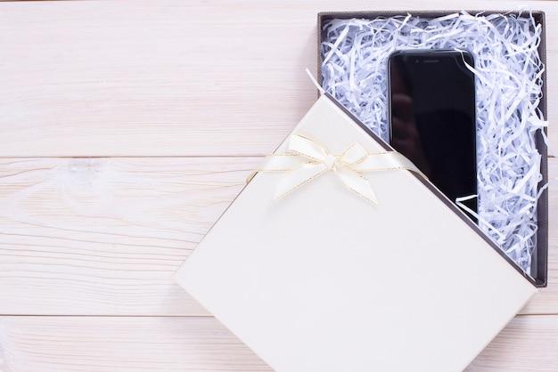 Caixa de presente com luz de fundo de madeira. celular Foto Premium