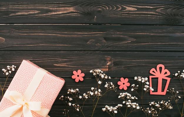Caixa de presente com ramos de flores na mesa de madeira Foto gratuita