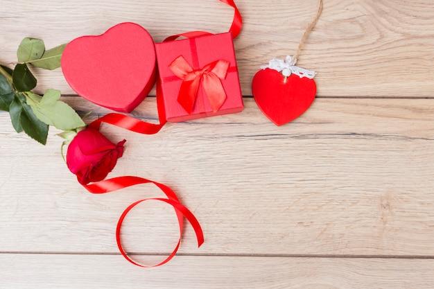 Caixa de presente com rosa vermelha na mesa Foto gratuita