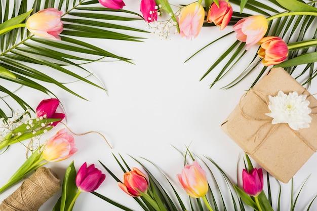 Caixa de presente com tulipas e palm Foto gratuita