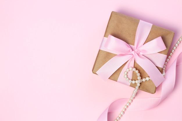 Caixa de presente com um laço rosa e pérola em um fundo rosa pastel. estilo liso leigo. Foto Premium