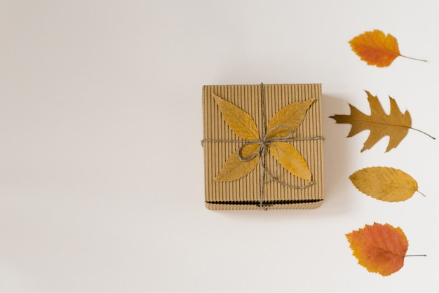 Caixa de presente de artesanato, amarrada com barbante com um arco e folhas caídas de outono. folhas amarelas e vermelhas. descontos de compras de outono. Foto Premium