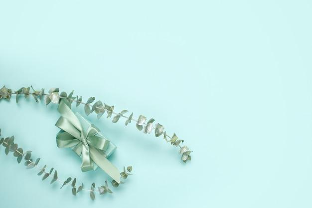 Caixa de presente de cor verde natural com laço de cetim e raminhos de eucalipto na cor menta. composição elegante primavera monocromático com espaço de cópia. Foto Premium