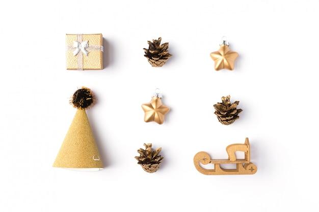 Caixa de presente de natal com enfeites de ouro, bolas, estrelas e cones em um branco Foto Premium