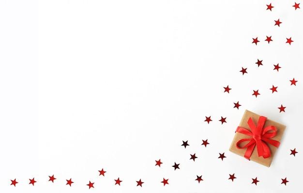 Caixa de presente de natal com fita vermelha com confetes de estrelas. Foto Premium