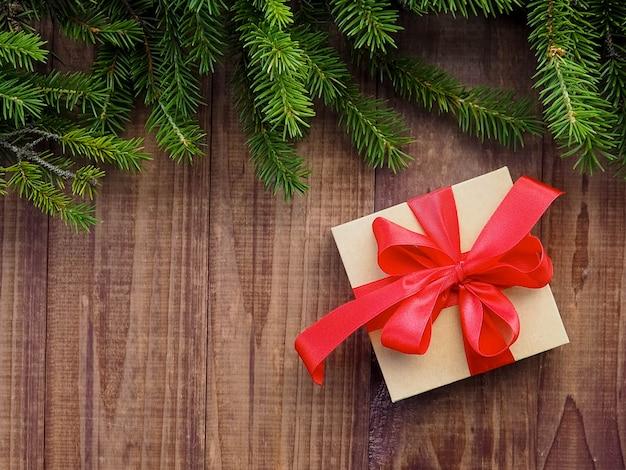 Caixa de presente de natal com fita vermelha na madeira, presentes de natal com enfeites Foto Premium