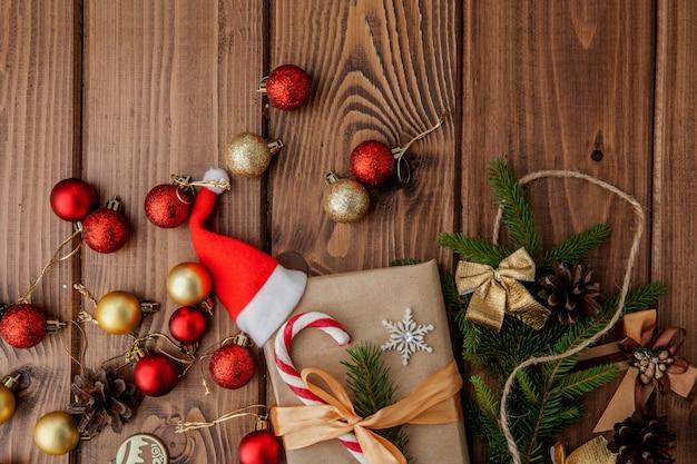 Caixa de presente de natal, decoração de alimentos e galho de árvore do abeto na mesa de madeira Foto Premium