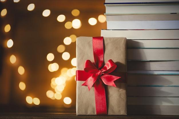 Caixa de presente de natal e pilha de livros com luzes de fada Foto Premium