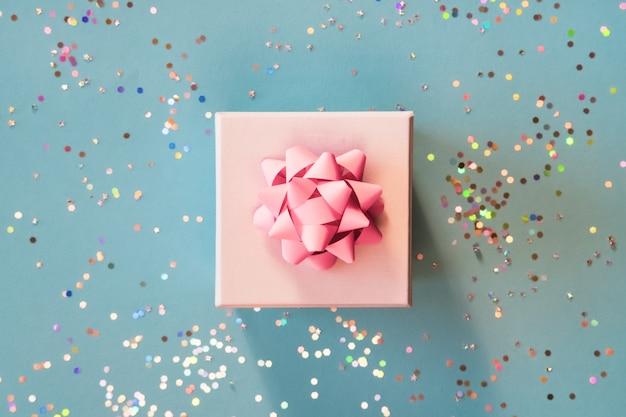 Caixa de presente de prata branca com laço rosa sobre fundo azul verde no apartamento moderno leigos composição com brilhos dourados. Foto Premium